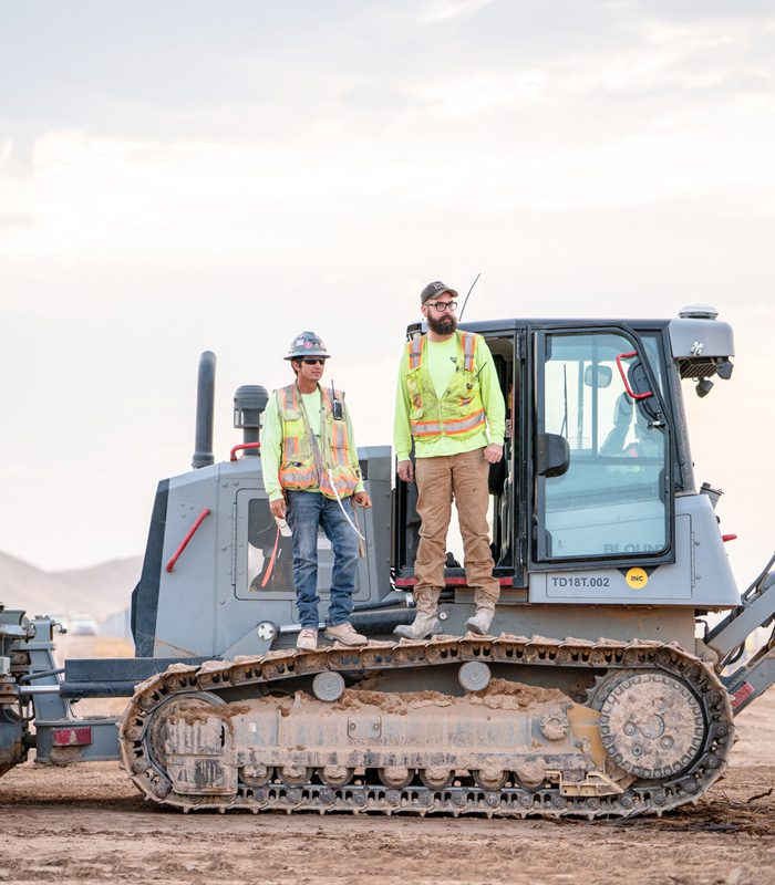 Two Blount Employees Standing on Equipment